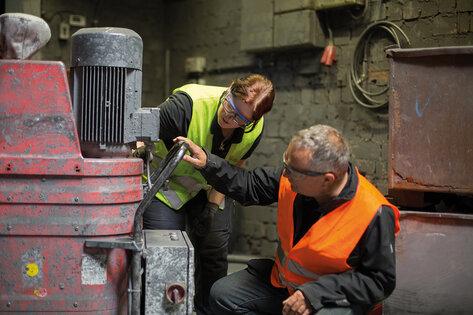 Ruwac Kundendienst Mitarbeiterin und Ruwac Verkaufsberater schauen sich einen Industriesauger beim Kunden vor Ort an