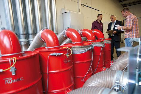 Продавец-консультант компании Ruwac GmbH разговаривает с клиентами возле пылесосов